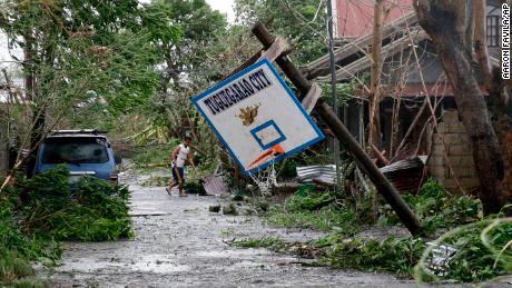 A resident walks beside a toppled basketball court after Typhoon Mangkhut barreled across Tuguegarao city, Cagayan province.