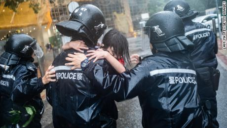 Police officers carry a girl out of a collapsed school in Hong Kong on Sunday.