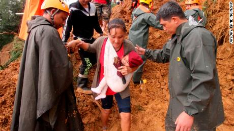Rescuers assist a mother and her child as they move to safer grounds following landslides in the Benguet province in northern Philippines on Sunday.